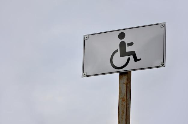 Een verkeersteken dat op de kruising van een weg voor gehandicapten wijst