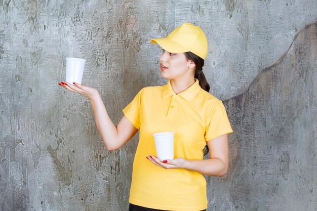Een verkoopster in geel uniform die twee plastic bekers drank vasthoudt en er een aan de andere persoon geeft