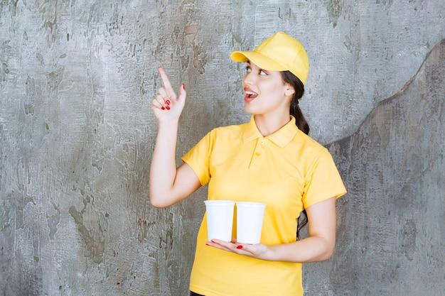 Een verkoopster in geel uniform die twee plastic bekers drank vasthoudt en naar iets wijst.