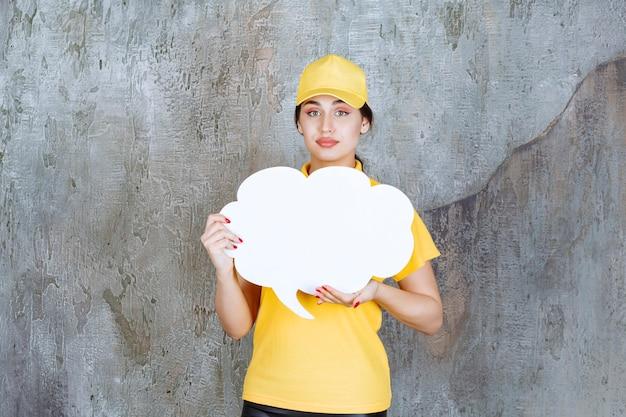Een verkoopster in geel uniform met een infobord in de vorm van een wolk