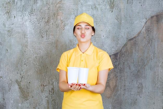 Een verkoopster in geel uniform met twee plastic bekers drank en een kus.