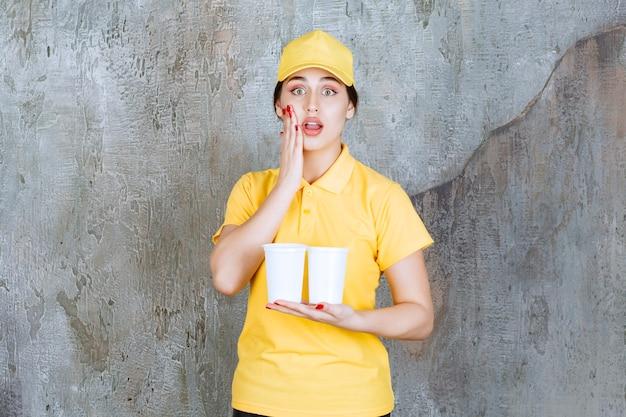 Een verkoopster in geel uniform met twee plastic bekers drank en kijkt gestrest en doodsbang