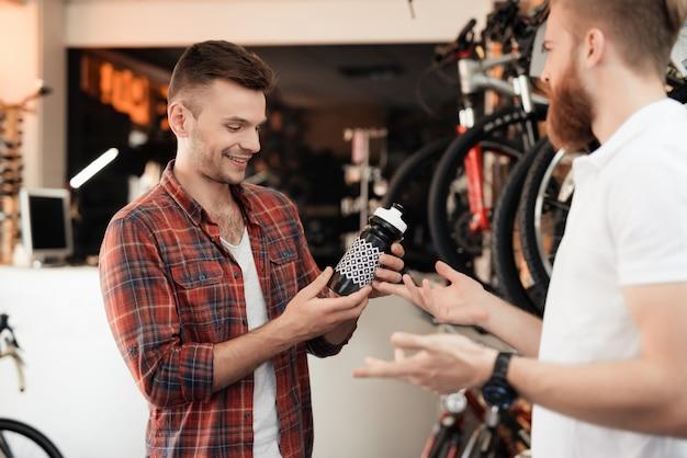 Een verkoper helpt een jonge koper bij het kiezen van een waterfles.