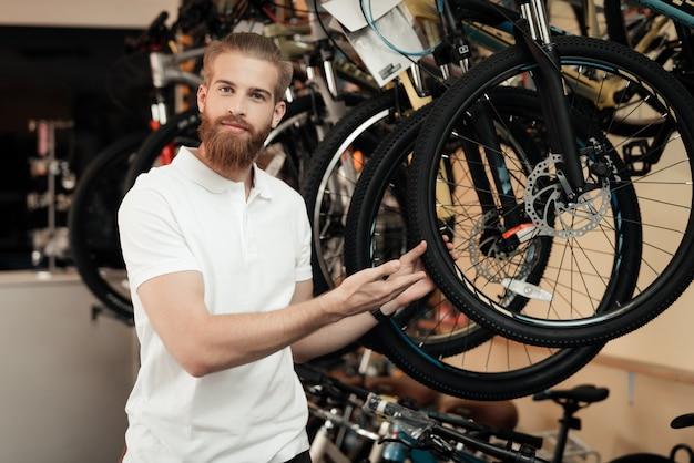 Een verkoper in een fietswinkel staat in de buurt van een fiets