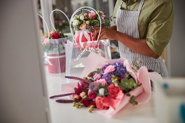 Een verkoper van een bloemenwinkel die een pot met bloeiende bloemen in een plastic zak bij een boeket stopt