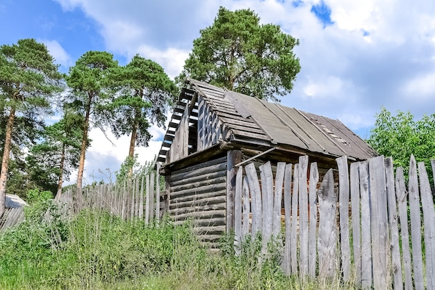 Een verlaten schuur en een oud houten hek staan aan de rand van het dorp bij het bos