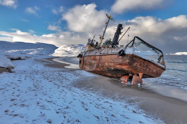 Een verlaten vissersschoener die door een storm aangespoeld was. barentszzee, het kola-schiereiland, teriberka, rusland