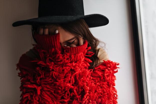 Een verlegen vrouw bedekt haar gezicht met haar handen. portret van een vrouw in zwarte hoed en rode gebreide trui in witte kamer.