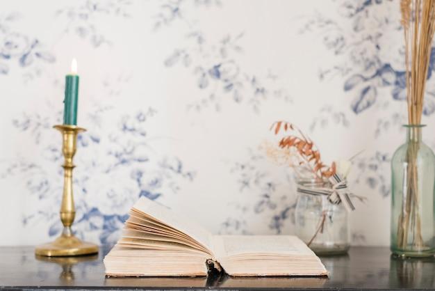 Een verlichte kaars en boek op bureau tegen behang