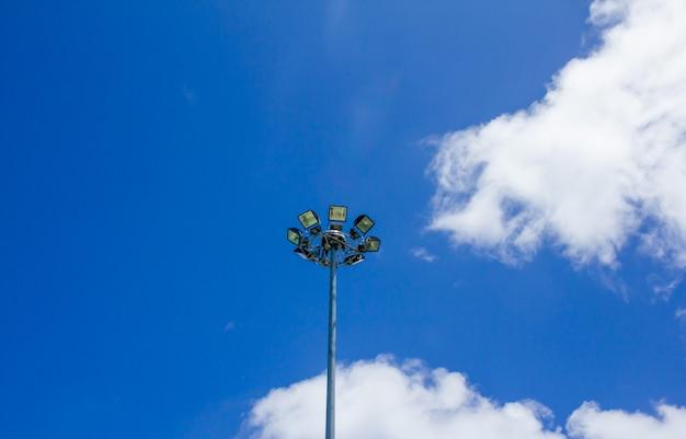 Een verlichtingslamp op een paal tegen de blauwe hemel, sportlicht met blauwe hemelwolkachtergrond