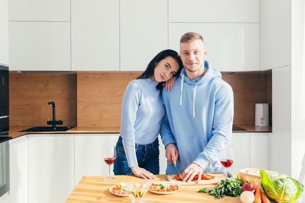 Een verliefd jong stel, een man en een vrouw, koken samen een diner en maken plezier in een nieuw appartement