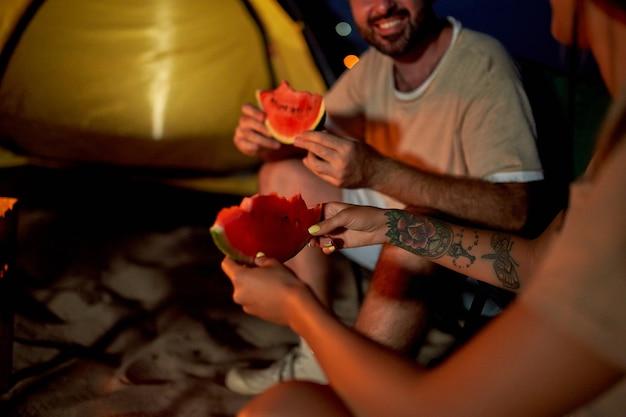 Een verliefd jong stel zit op klapstoelen bij de tent bij het vuur, eet watermeloen en heeft 's avonds plezier op het strand aan zee.