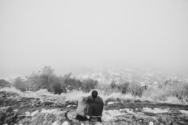Een verliefd koppel wandelingen in het sneeuwpark gelukkig wintervakantie zwart-wit foto