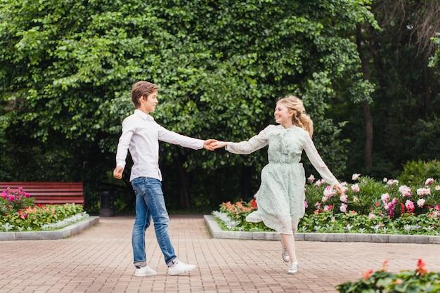 Een verliefd paar, een jong meisje en een man, staande in het park, knuffels, vergadering, kussen, boeket