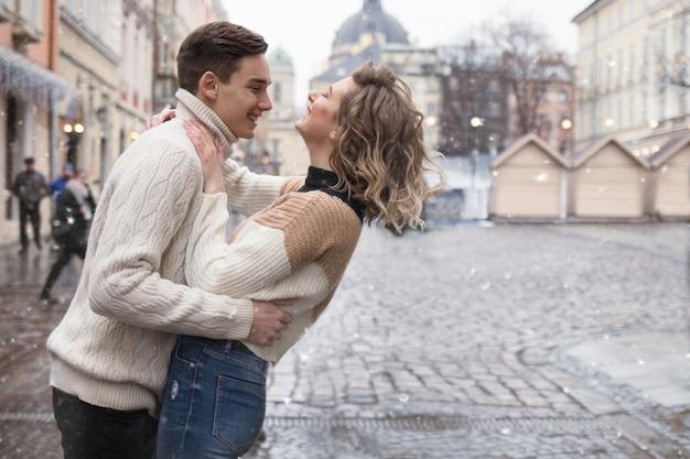 Een verliefd paar in de stad onder de sneeuw die lacht en naar elkaar kijkt