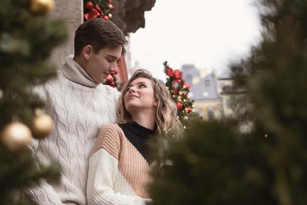 Een verliefd paar in een nieuwjaarsstad kijken elkaar aan en glimlachen