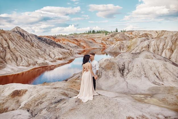 Een verliefd paar kijken elkaar recht aan in een rotsachtig landschap