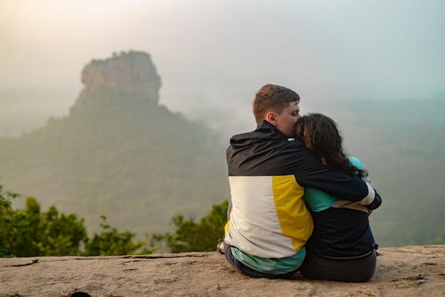 Een verliefd paar op een rots bewondert de prachtige uitzichten.