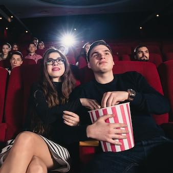 Een verliefd stel dat flirt in de bioscoop en popcorn eet