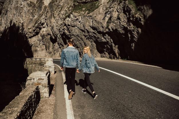 Een verliefd stel, een man en een meisje lopen in de verte over de weg, hand in hand.