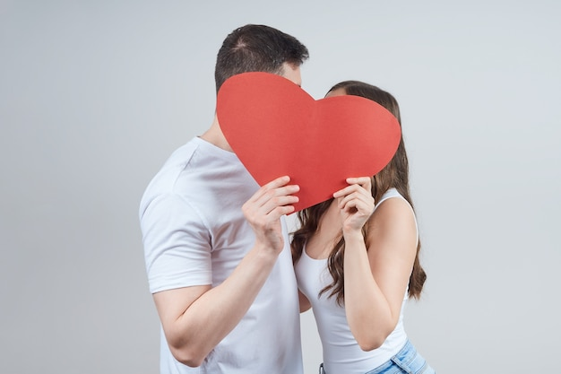 Een verliefd stel houdt een papieren rood hart vast, dat hun gezichten bedekt. fijne valentijnsdag.
