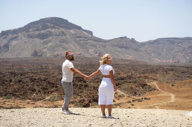 Een verliefd stel houdt elkaars hand vast in de krater van de teide-vulkaan