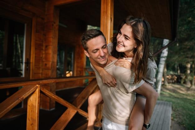 Een verliefd stel in de natuur. de man houdt het meisje op zijn rug.