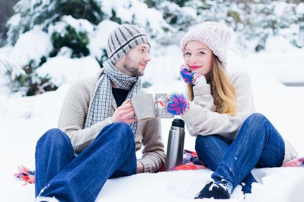 Een verliefd stel in warme kleren zit in de sneeuw en houdt een kopje vast met een warme drank