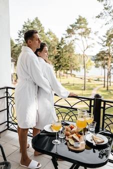 Een verliefd stel knuffelend op een hotelbalkon in hun badjassen met ontbijt op tafel