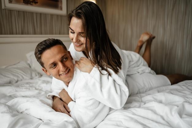 Een verliefd stel liggend op een bed in badjassen