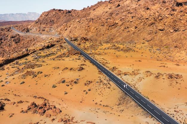 Een verliefd stel loopt langs de weg in de krater van de teide-vulkaan