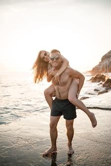 Een verliefd stel loopt langs het strand aan zee. jong gezin bij zonsondergang aan de middellandse zee. vakantieconcept. een vrouw in een zwempak en een man in korte broek bij zonsondergang aan zee. selectieve aandacht.
