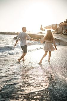 Een verliefd stel loopt op het strand in de buurt van de zee. jong gezin bij zonsondergang aan de middellandse zee. zomer vakantie concept. selectieve focus