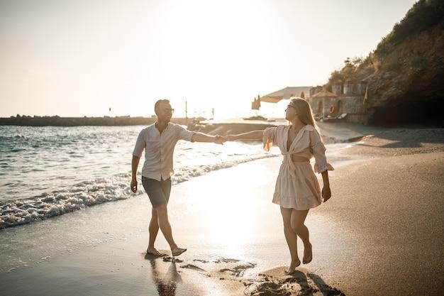 Een verliefd stel loopt op het strand in de buurt van de zee. jong gezin bij zonsondergang aan de middellandse zee. zomer vakantie concept