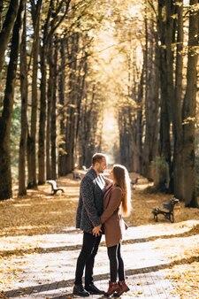 Een verliefd stel omhelst elkaar in een herfstpark bij zonsondergang