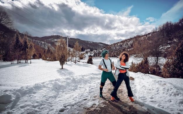 Een verliefd stel staat en heeft plezier in de sneeuw op een zonnige winterdag.
