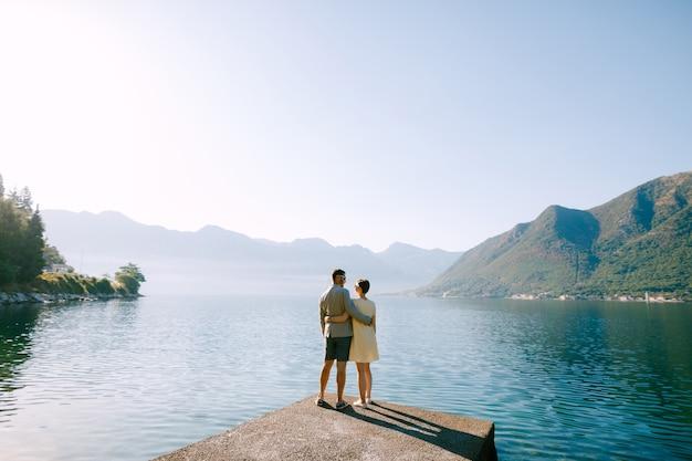 Een verliefd stel staat knuffelend op een pier in de baai van kotor bij perast tegen de achtergrond van