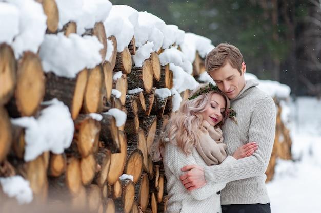 Een verliefd stel verwarmt en omhelst elkaar. winter bruiloft. bruidegom kuste zijn bruid teder in haar tempel