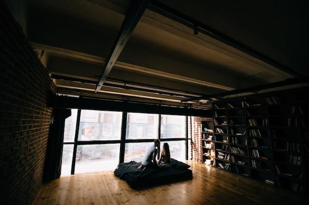 Een verliefd stel zittend op een matras in een loft.