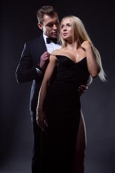 Een verliefde man en een vrouw in modieuze avondjurken omhelzen elkaar