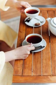Een verliefde paar zit in kamerjassen en drinkt thee op een houten tafel