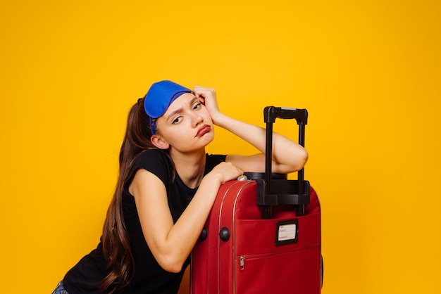 Een vermoeid jong meisje heeft haar koffer ingepakt op reis, wachtend op haar vliegtuig