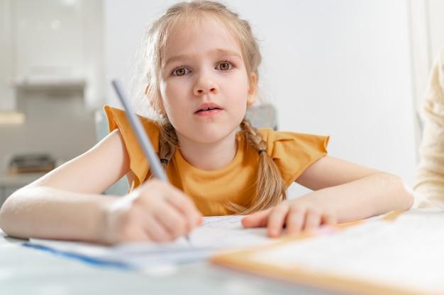 Een vermoeid schoolmeisje doet haar huiswerk. complexiteit van correct en mooi handschrift. er is geen verlangen om te leren. familie- en afstandsonderwijs