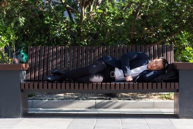 Een vermoeide aziatische arbeider ligt voor het bedrijf tijdens een pauze van het werk. rust na een dag hard werken op een bankje in het park