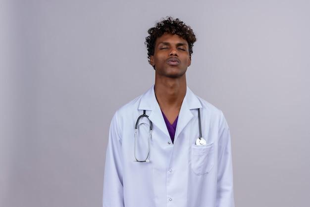 Een vermoeide jonge knappe donkere mannelijke arts met krullend haar die een witte jas draagt met een stethoscoop die zijn ogen sluit en nadenkt