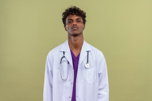 Een vermoeide jonge knappe donkere mannelijke arts met krullend haar die witte jas met stethoscoop draagt en aan een groene ruimte denkt