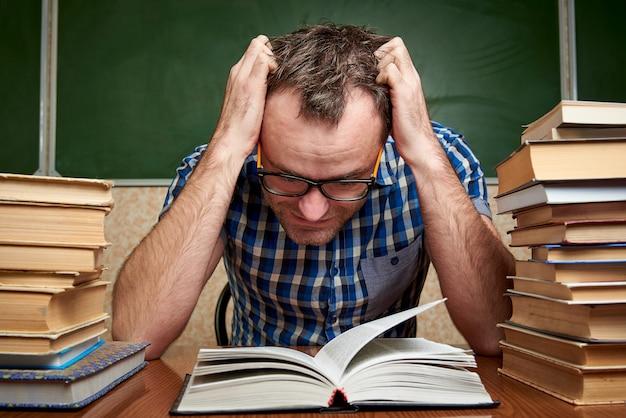 Een vermoeide jonge man leest een boek.