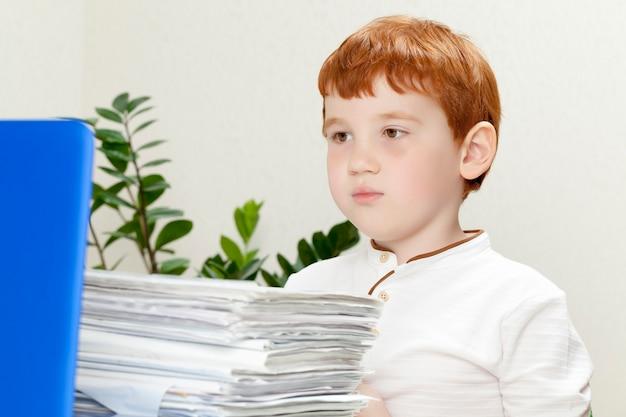 Een vermoeide jongen met rood haar zit met een groot aantal vellen papier en documenten voor zijn werk