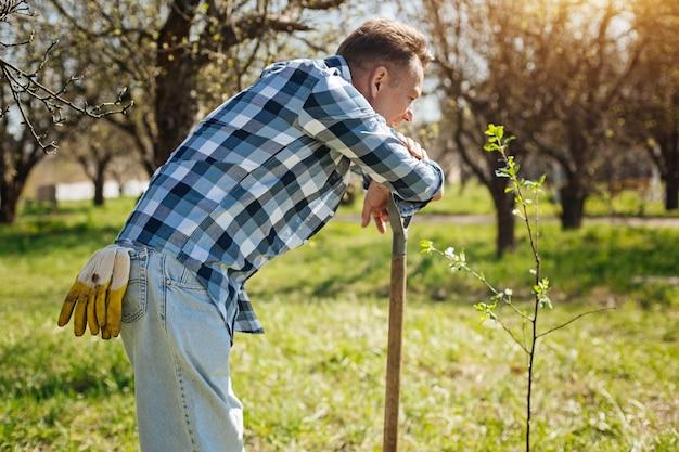 Een vermoeide maar tevreden man die een stap terug doet van een werk terwijl hij op het handvat van een tuinschop leunt