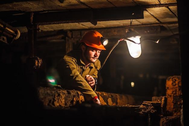 Een vermoeide mijnwerker in een kolenmijn kijkt naar het licht. werk in een kolenmijn.